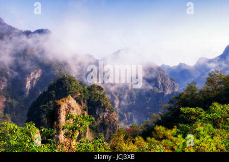 A low hanging cloud against blue sky in the early morning at Fangdong Scenic Area on Yandangshan mountains located - Stock Photo