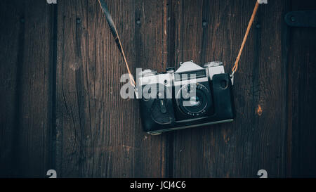 Old gray zenith in a brown leather case hanging on a wooden wall background. - Stock Photo