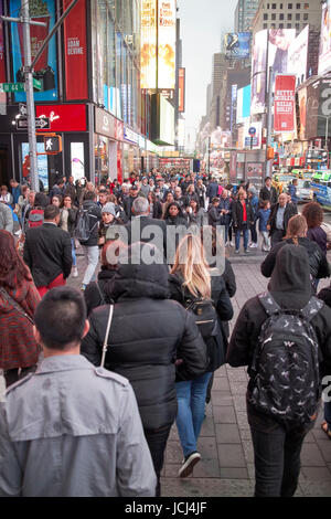 people crossing crosswalk full busy sidewalk in the evening evening in Times Square New York City USA - Stock Photo