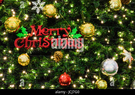 Merry Christmas sign on the tree that is decorated beautifully - Stock Photo