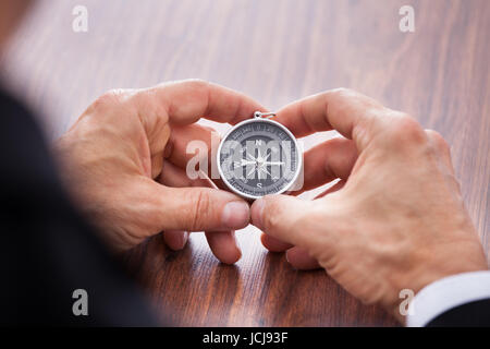Close-up Of Hand Holding Compass On White Background - Stock Photo