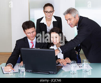 Four diverse professional businesspeople having a discussion and brainstorming session gathered around a laptop - Stock Photo
