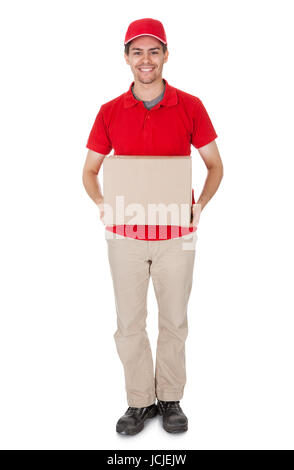 Smiling male courier in a red shirt and cap delivering a parcel in a brown cardboard box - Stock Photo