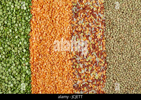 Dried legumes in vertical layers, from left to right: green split peas, red lentils, mix of red Thai rice, white - Stock Photo