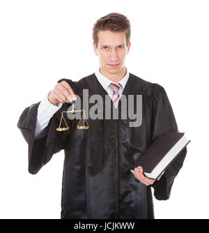 Young Male Judge Holding Golden Scales And Book Over White Background - Stock Photo