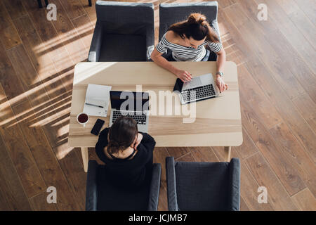 startup business and new mobile technology concept with young couple in modern bright office interior working on - Stock Photo