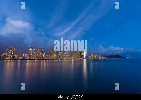 A view of Diamond Head and Waikiki at dusk from Ala Moana beach park. - Stock Photo