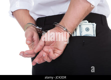 Closeup view from behind of a man in handcuffs with dollar banknotes in his pocket conceptual of crime and corruption - Stock Photo
