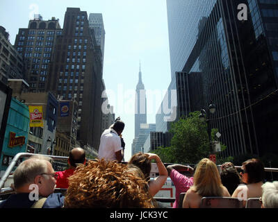 Tour bus ride through New York City with the Empire State Building off in the distance - Stock Photo