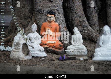 Buddha Statues detail under a tree - Stock Photo