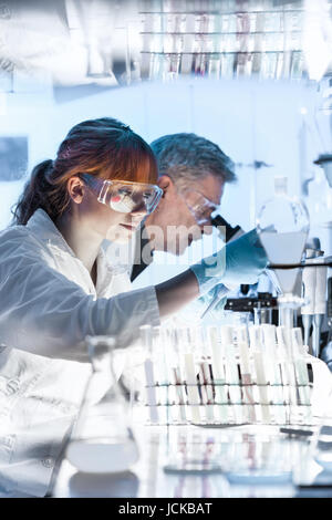 Health care researchers working in life science laboratory. Young female research scientist and senior male supervisor - Stock Photo