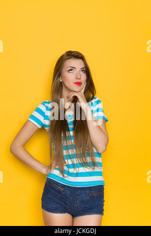 Young woman in blue striped shirt and jeans shorts holding hand on chin, grimacing and looking up. Three quarter - Stock Photo