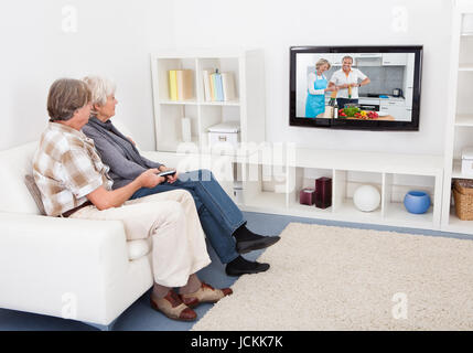 Senior Couple Watching Television Showing Recipe At Home - Stock Photo