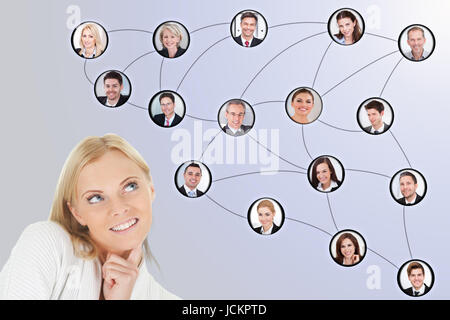 Digital composite image of thoughtful businesswoman looking at team connected together - Stock Photo