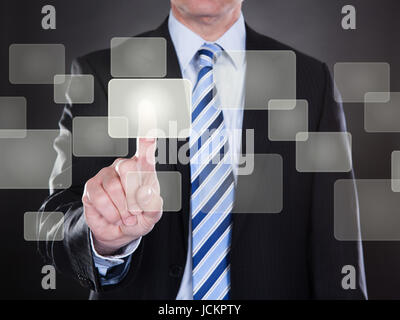 Midsection of businessman pushing button on transparent screen - Stock Photo
