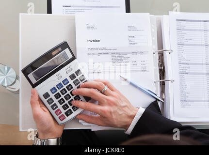 Cropped image of businessman calculating invoice at desk in office - Stock Photo