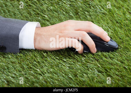 Closeup of businessman's hand using computer mouse on grass - Stock Photo
