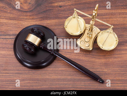 Judge gavel and scales with money on wooden desk - Stock Photo