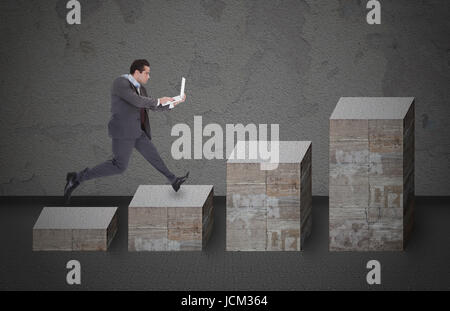 Full length side view of businessman with laptop running on bar graph made from stones - Stock Photo