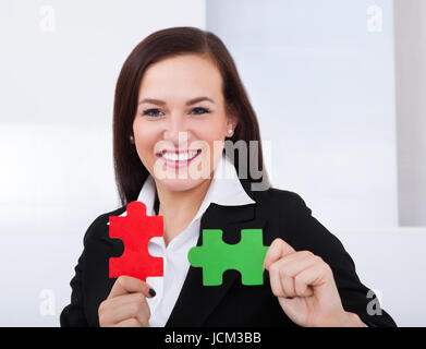 Portrait of happy businesswoman holding puzzle pieces in office - Stock Photo