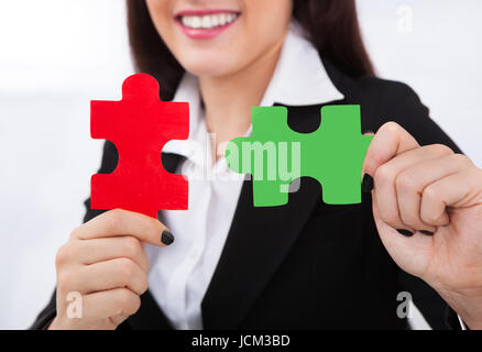 Close-up of happy businesswoman holding puzzle pieces in office - Stock Photo