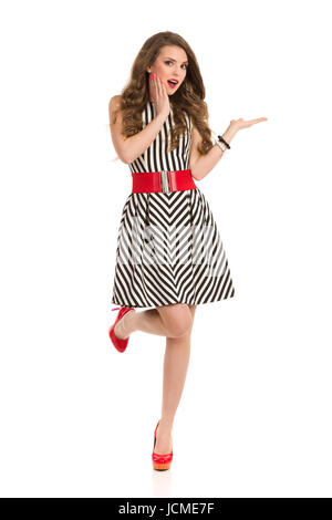 Surprised attractive woman in black and white striped dress and high heels standing on one leg, holding hand on - Stock Photo