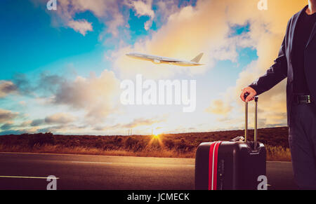 Business man with traveling luggage standing against landscape scene and passenger jet plane flying over sky . - Stock Photo