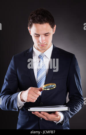 Young businessman analyzing documents with magnifying glass against black background - Stock Photo