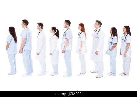 Large diverse group of medical staff in white uniforms with stethoscopes around their necks standing in a queue - Stock Photo