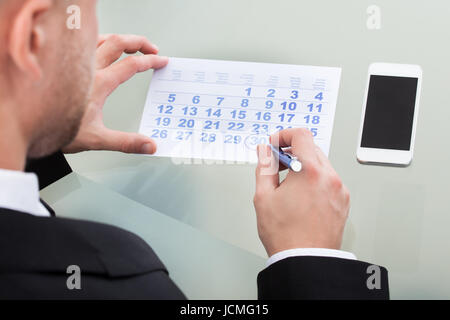 Businessman marking his dairy schedule checking for appointments and meetings as his mobile phone lies alongside - Stock Photo