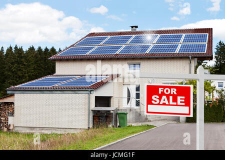 For sale sign in front of house with solar panels on roof - Stock Photo