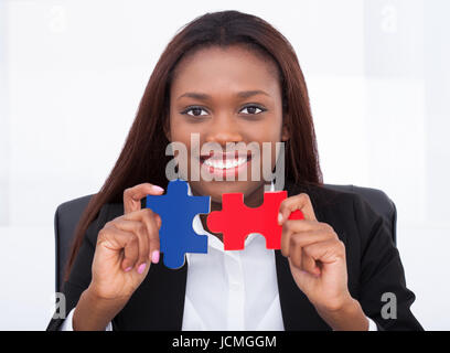 Portrait of confident businesswoman holding puzzle pieces in office - Stock Photo