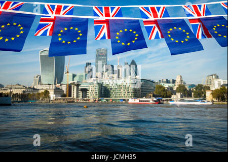 European Union and Union Jack bunting flags flying over the London skyline of the financial City center at the River - Stock Photo