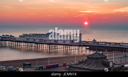 View of a sunset on  Brighton pier with a flock of birds - Stock Photo
