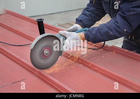 Cutting of heat insulated galvanized corrugated sandwich roof panel, workers hands and angle grinder tool - Stock Photo