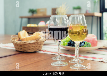 Wine with bread in basket and fruit on the wooden table in restaurant. - Stock Photo