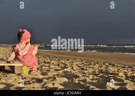 Illuminated by the rising sun little girl sitting on the beach and looking at the approaching storm. - Stock Photo