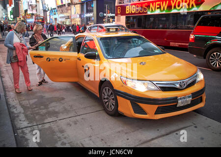 two women getting into a yellow cab in the evening in Times Square New York City USA - Stock Photo