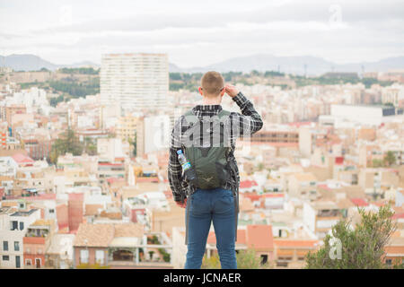 Traveller looks out over view of the city. Alicante in Spain - Stock Photo