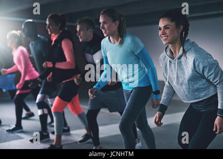 Group of young athletes working out in an urban indoor car park lining up ready to run a race or practice their - Stock Photo