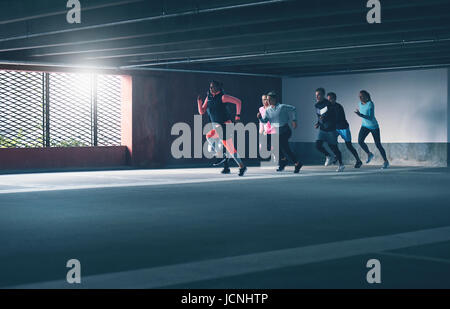 Group of determined young athletes urban running sprinting through a covered commercial car park in a training workout, - Stock Photo