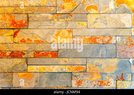 Closeup of red and orange rough modern stonewall background - Stock Photo