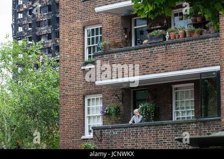 London, UK. 16th June, 2017. A woman stands on a balcony in a block immediately in front of the burnt out hulk of - Stock Photo