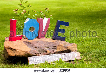 The word love spelled out in books that have been cut into letters sitting atop a large rock . - Stock Photo