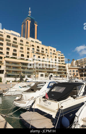 Boats moored in Portomaso Harbour St Julians Bay Malta in front of the Hilton hotel on a sunny summer day - Stock Photo