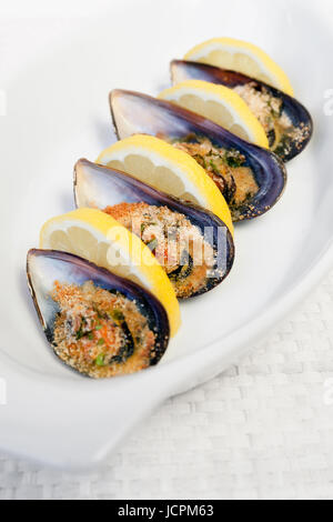 Grilled mussels cooked in the oven, accompanied by slices of lemon, grated pan and parsley. Mussels cooked on white - Stock Photo