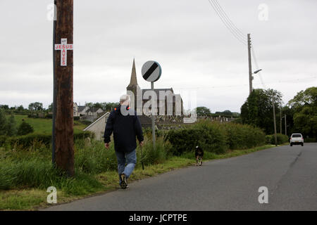 A man walks his dog down the Derryanvil Road close to Drumcree Church, Portadown 20 years since the Drumcree standoff - Stock Photo
