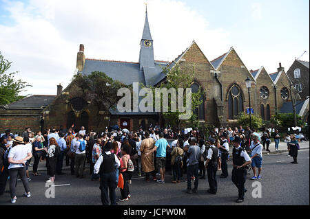 Crowds gather outside St Clement's Church in west London, which has provided shelter and support for people affected - Stock Photo