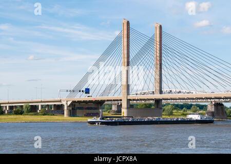 Inland tanker sailing downstream on Waal river and Martinus Nijhoff Bridge, Zaltbommel, Gelderland, Netherlands - Stock Photo