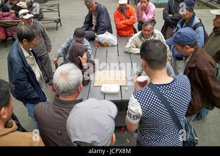 crowd watching two men play xiangqi chinese chess in columbus park chinatown New York City USA - Stock Photo